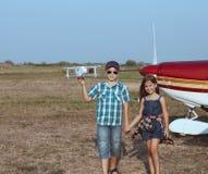 Pilote de petit garçon et de petite fille avec l'avion fait main Photo libre de droits