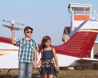 Pilote de petit garçon et de petite fille avec l'avion fait main Photo stock