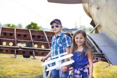 Pilote de petit garçon et de petite fille avec l'avion fait main Photographie stock