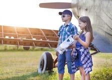 Pilote de petit garçon et de petite fille avec l'avion fait main Image libre de droits