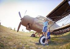 Pilote de petit garçon et de petite fille près du rétro avion Images libres de droits