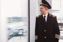 Pilote de sourire hilare se tenant dans le terminal Photos stock