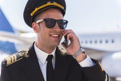 Pilote de sourire joyeux parlant du téléphone Image stock