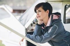 Pilote féminin de sourire de jeunes se penchant sur un avion Photos stock