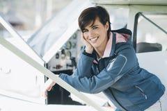 Pilote féminin de sourire de jeunes se penchant sur un avion Photo libre de droits