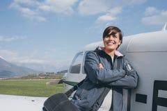 Pilote féminin de sourire posant avec son avion Image stock