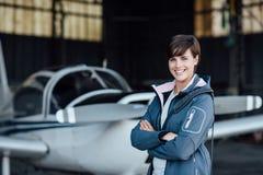 Pilote féminin de sourire posant avec son avion Photo libre de droits