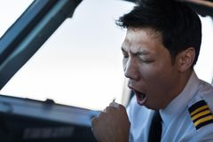 Pilote masculin épuisé dans l'avion d'habitacle, vol photos libres de droits
