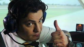 Pilote professionnel dépendant montrant des pouces vers le haut du signe, appréciant son travail, profession clips vidéos