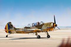 Piloten av flygplanet för Yak 52 från laget Iacarii Acrobati saluterar folkmassan Arkivfoto