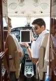 Piloten, die Digital-Tablet im Cockpit verwenden lizenzfreie stockfotos