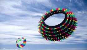 Piloter des cerfs-volants de forme annulaire colorés au-dessus de plage dans l'océan étaye Photographie stock libre de droits