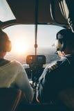 Piloter som flyger en helikopter på solig dag Arkivbild