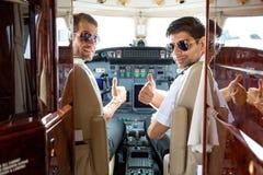 Piloter som gör en gest tummar upp i cockpit royaltyfri bild