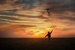 Piloter un cerf-volant Le gar?on court ? travers le champ avec un cerf-volant Coucher du soleil lumineux image stock