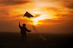Piloter un cerf-volant Le gar?on court ? travers le champ avec un cerf-volant Silhouette d'un enfant contre le ciel Coucher du so images stock