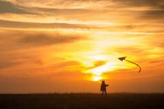 Piloter un cerf-volant Le gar?on court ? travers le champ avec un cerf-volant Silhouette d'un enfant contre le ciel Coucher du so image libre de droits