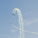 Pilotes acrobatiques aériens avec ses avions colorés s'exerçant dans le ciel bleu Photos stock