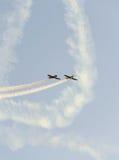 Pilotes acrobatiques aériens avec ses avions colorés s'exerçant dans le ciel bleu Image libre de droits