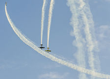 Pilotes acrobatiques aériens avec ses avions colorés s'exerçant dans le ciel bleu Images libres de droits