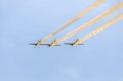 Pilotes acrobatiques aériens s'exerçant dans le ciel bleu, avions avec de la fumée colorée de trace Photos libres de droits