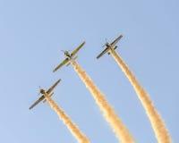 Pilotes acrobatiques aériens s'exerçant dans le ciel bleu, avions avec de la fumée colorée de trace Photos stock