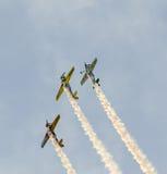 Pilotes acrobatiques aériens s'exerçant dans le ciel bleu, avions avec de la fumée colorée de trace Photo stock