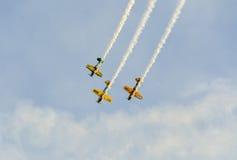 Pilotes acrobatiques aériens s'exerçant dans le ciel bleu, avions avec de la fumée colorée de trace Images stock