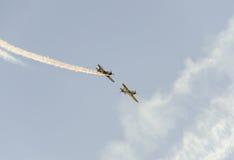 Pilotes acrobatiques aériens s'exerçant dans le ciel bleu, avions avec de la fumée colorée de trace Images libres de droits