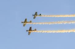Pilotes acrobatiques aériens s'exerçant dans le ciel bleu, avions avec de la fumée colorée de trace Image libre de droits