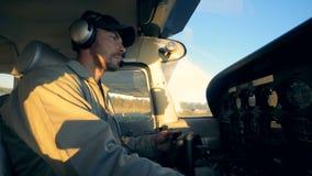Piloti maschii dell'aviatore un aereo in una cabina di pilotaggio, vista laterale stock footage