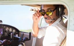 Piloto atractivo en el avión Imagenes de archivo