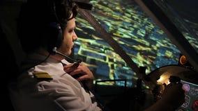 Piloto comercial en aeroplano que controla uniforme hermoso sobre ciudad de la noche almacen de metraje de vídeo