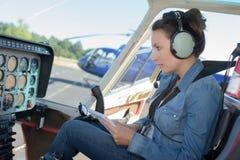 Piloto de sexo femenino del helicóptero que lee el manual mientras que se sienta en carlinga imagen de archivo