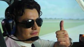 Piloto de sexo masculino que goza el suyo trabajo, sentándose en la carlinga del avión de pasajeros, mostrando los pulgares para  almacen de video