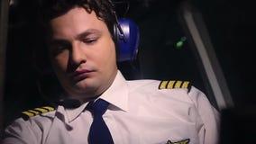 Piloto de sexo masculino serio en el panel de mirada uniforme de los mandos de vuelo de la aviación civil en almacen de video