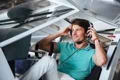 Piloto de sorriso do homem que senta-se na cabine de aviões pequenos Fotografia de Stock Royalty Free