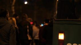 Piloto del coche de la emergencia en el fondo de la muchedumbre móvil de gente de protesta en un camino de la noche almacen de metraje de vídeo