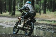 Piloto do motocross em um terreno molhado e enlameado Fotografia de Stock Royalty Free