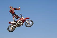 Piloto do motocross que executa o conluio com a motocicleta no meio do ar contra o céu Fotografia de Stock