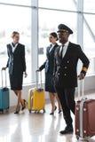 piloto e comissárias de bordo novos com passeio da bagagem imagens de stock royalty free