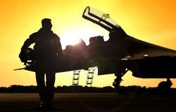Piloto en el campo de aviación que se niega a afrontar el avión de combate fotografía de archivo libre de regalías