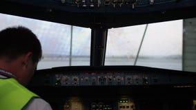 Piloto en el vuelo de la carlinga El interior de la cabina de aviones con el panel y el volante El técnico en almacen de video