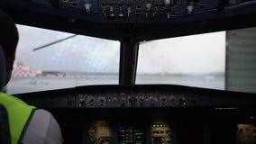 Piloto en el vuelo de la carlinga El interior de la cabina de aviones con el panel y el volante El técnico en almacen de metraje de vídeo