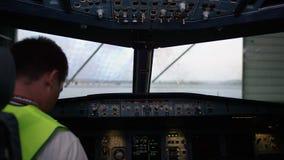 Piloto en el vuelo de la carlinga El interior de la cabina de aviones con el panel y el volante El técnico en metrajes