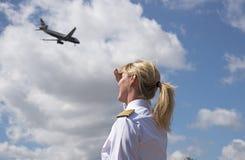 Piloto fêmea com um avião de passagem de passagem no céu fotos de stock