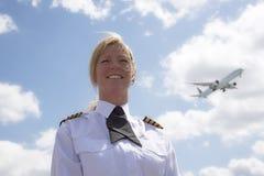 Piloto fêmea com um avião de passagem de passagem no céu fotografia de stock royalty free