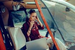 Piloto fêmea experiente sério que tem a conexão com o operador do voo fotografia de stock