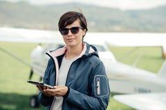 Piloto fêmea que usa uma tabuleta imagem de stock