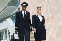 Piloto And Flight Attendant que anda fora da construção Imagem de Stock